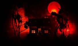 Old house with a Ghost in the moonlit night or Abandoned Haunted Horror House in fog. Old mystic villa with surreal big full moon. Horror Halloween concept royalty free stock image