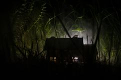 Old house with a Ghost in the moonlit night or Abandoned Haunted Horror House in fog. Old mystic villa with surreal big full moon. Horror Halloween concept stock photography