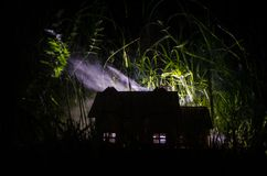 Old house with a Ghost in the moonlit night or Abandoned Haunted Horror House in fog. Old mystic villa with surreal big full moon. Horror Halloween concept stock image