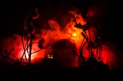 Old house with a Ghost in the moonlit night or Abandoned Haunted Horror House in fog. Old mystic villa with surreal big full moon. Royalty Free Stock Photos