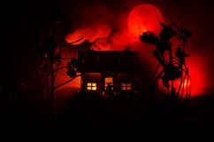 Old house with a Ghost in the moonlit night or Abandoned Haunted Horror House in fog. Old mystic villa with surreal big full moon. Royalty Free Stock Photography