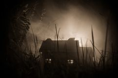 Old house with a Ghost in the moonlit night or Abandoned Haunted Horror House in fog. Old mystic villa with surreal big full moon. Horror Halloween concept stock photo