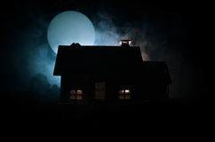 Old house with a Ghost in the moonlit night or Abandoned Haunted Horror House in fog, Old mystic villa with surreal big full moon. Stock Photo