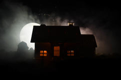Old house with a Ghost in the moonlit night or Abandoned Haunted Horror House in fog, Old mystic villa with surreal big full moon. Stock Image