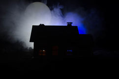 Old house with a Ghost in the moonlit night or Abandoned Haunted Horror House in fog, Old mystic villa with surreal big full moon. Royalty Free Stock Photos