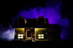 Old house with a Ghost in the moonlit night or Abandoned Haunted Horror House in fog. Old mystic villa with surreal big full moon. Royalty Free Stock Image