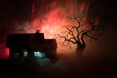 Old house with a Ghost at night with spooky tree or Abandoned Haunted Horror House in toned foggy sky with light. Old mystic build. Ing in dead tree forest royalty free illustration