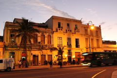 Old house in the historic center of Havana at night. The street is brightly lit with yellow lamps. There are some tourists and local people walking nearby stock photo