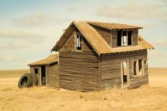 An old house holding up some tractor tires. An old abandoned farmhouse outside of Keene North Dakota holding up a couple of tractor tires Stock Photography