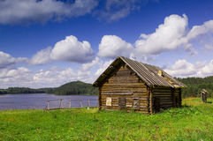 Old house at the lake. Old north Russian house on the lake shore Stock Photography