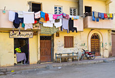 The old house. LUXOR, EGYPT - OCTOBER 7, 2014: The old yellow house with the laundry on the ground floor, on October 7 in Luxor Royalty Free Stock Photo