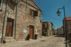Old house made of stone on deserted alley. Old house facade made of rough stone with wooden door on deserted alley, in a sunny day at Belmonte. A cute small town royalty free stock photo