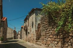 Old house made of stone on deserted alley. Old stone wall with green shrubs and worn house facade on deserted alley, in a sunny day at Belmonte. A cute small royalty free stock photos