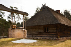 Old house and mallet. An old mallet used to call families together in an open air museum Royalty Free Stock Photography