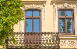 Old house in the Modernist style. Architectural fragment of an old house in the Modernist style with a balcony decorated with beautiful forging stock images