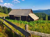 Old house in the mountains. An old cabin in the mountains among the fields Royalty Free Stock Photos