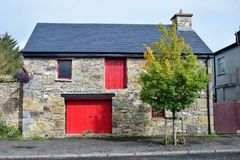 An old house in Mountshannon with red doors. County Clare, Ireland stock images