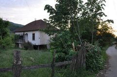 Old stone house with a tiled roof around the house growing dense green grass horizontal photo. An old house, a house of mud. East Serbia Royalty Free Stock Photography