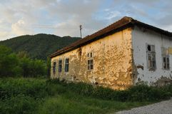 Old stone house with a tiled roof around the house growing dense green grass horizontal photo. An old house, a house of mud. East Serbia Stock Images