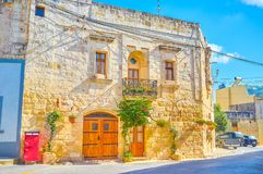 The old house in Naxxar, Malta. The old stone house with small windows and huge entrance wooden gates, Naxxar town, Malta royalty free stock photography