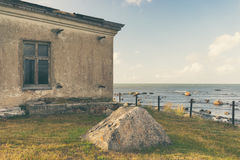 Old house near the Baltic Sea. A stone fisherman`s house on the shore of the Baltic Sea next to the Tahkuna lighthouse on the background of the horizon Royalty Free Stock Photo