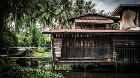 Old house near river in Nonthaburi, Thailand. Nonthaburi, Thailand - September 10, 2016: Old house near river in Nonthaburi, Thailand Stock Image