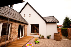 Old house new design architecture. An old house with new design renovation project - new elevation, neat pebble backyard and wooden panels terrace Stock Image