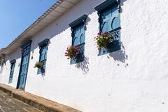 Old house painted white with blue windows and flowers. Old house wall on white a some windows Royalty Free Stock Image