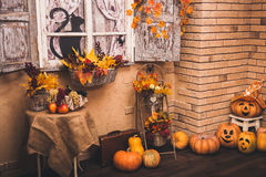 Old house patio in autumn season. Old house patio in autumn season: shutters entwined with yellow leaves, halloween pumpkins lying on the floor Stock Photos