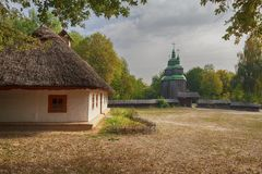 Old house of the peasants and church at the Museum of Pirogovo. Ukraine Stock Photo