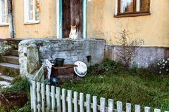 Old house with a porch and a cat. And a wooden fence royalty free stock photos