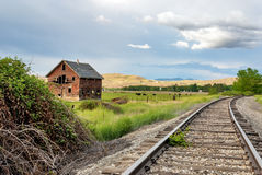 Old house and railroad tracks. Railroad tracks pass by an old house that is falling apart Stock Photography