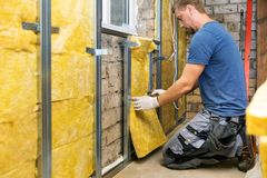 Construction worker insulating brick wall with glass wool royalty free stock photo