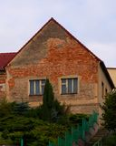 Old house with red bricks walls and peeling plaster Royalty Free Stock Photo