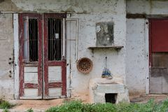 Old house red doors. Red doors weathered mirror and outdoor sink. Abandoned old house exterior Royalty Free Stock Image
