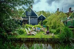 Old house on the river. Old house with attic Windows and chairs which stands on the river royalty free stock photos
