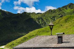 Old house roof with view on mountains. Alpine landscape along the Zillertal high road, Austria, Tyrol Stock Image