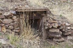 Old house or root cellar stone entrance. The underground home or storage room with the wooden door way was bermed into a desert badlands hillside and built with Stock Image