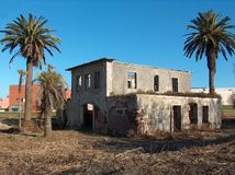 Old House in Ruins. Foto of an Old House in Ruins with surrounding palms in a blue sky background royalty free stock photos