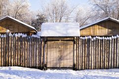 Old house in the Siberian forest fenced with palisade snow Royalty Free Stock Image