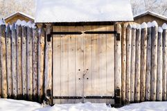 Old house in the Siberian forest fenced with palisade snow Stock Images
