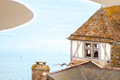 Old house on small river bank in France. Old vintage house with tiled roof and two gulls on it standing on small river bank in France. Curved narrow river with Royalty Free Stock Image