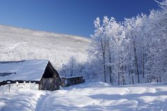 Old house in snowy mountains stock image