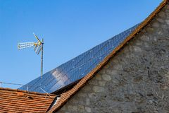 Old house with solar panels and TV antenna. Installed on roof close-up stock image