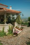 Old house with stairs leading to porch full of flowers in Monsanto. Charming old house facade with stairs leading to porch full of flowers, on hilly landscape in royalty free stock photo
