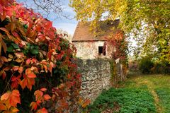 Old house and stone fence in autumn stock images
