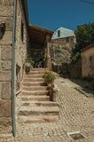 Old house with stone staircase and flower pots. Old house facade with stone staircase and flower pots on narrow deserted alley, in a sunny day Belmonte. A cute royalty free stock photo