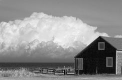 Old house and stormy clouds. Old house facing stormy clouds coming over the sea. Black and white photos- stock photos stock image