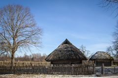 Old house with a straw roof in the blue sky in the spring stock photo