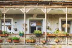 Old House in Tbilisi, Georgia with Beautiful Terrace. Ancient traditional wooden balcony decorated with lot of flowers and old royalty free stock image